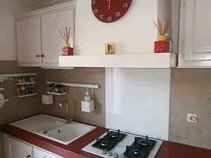 photo d'une cuisine rénovée représentant un évier, les plaques de cuisson et une hotte aspirante. La finition est en béton ciré et la crédence en verre sécurit.