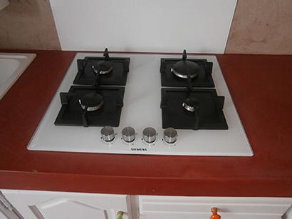 Photo d'une vue de dessus d'une plaque de cuisson au gaz et verre blanc. Le plan de travail est recouvert d'un béton ciré couleur terre de sienne