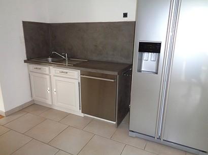 Photo légèrement de face et de côté du bloc évier et meuble sous-évier rénové avec effet béton ciré et portes de placard laqués blanc