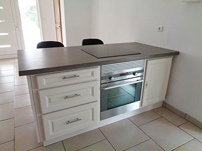 Photo vue côté cuisine de l'ilot comptoir où on peut voir des tiroirs, un four encastré et une porte de placard